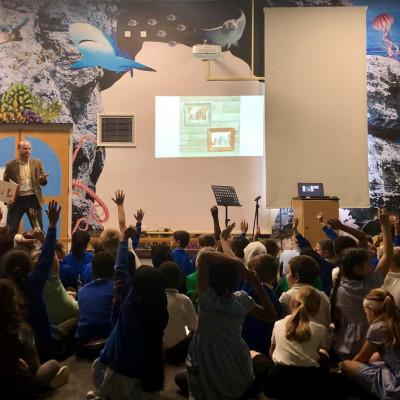 Chris Naylor-Ballesteros talks to children