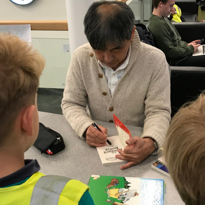Satoshi signing books for the children after his performance