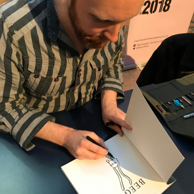Alexis does a little drawing alongside his signature