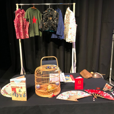 Chinese artefacts, including clothes, fans and a bamboo birdcage