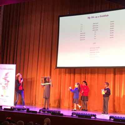 Some children come up onto stage to help Rachel perform her poem *My Life as a Goldfish*