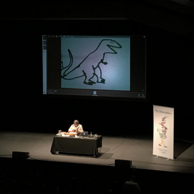 Satoshi draws a dinosaur on stage at Warwick Arts Centre